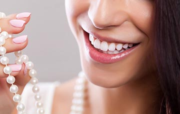 A women smiling at her white pearls